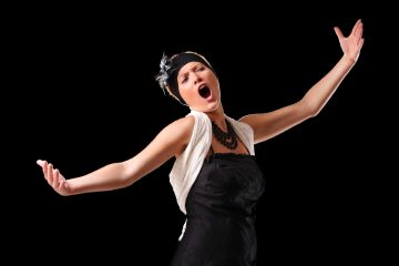 woman holding out arms belting out opera singing