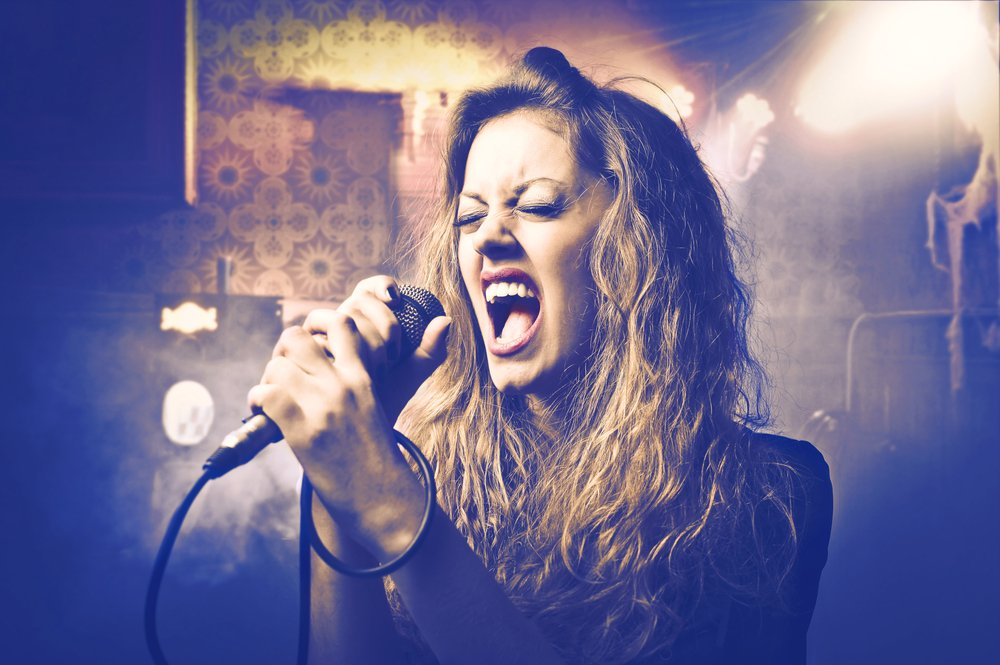 blonde girl screaming into microphone