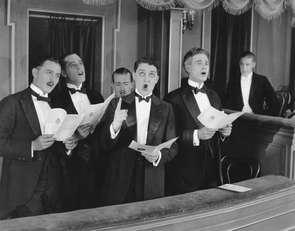 a group of guys singing harmony in black and white.