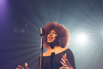 woman singing on stage hands moving.