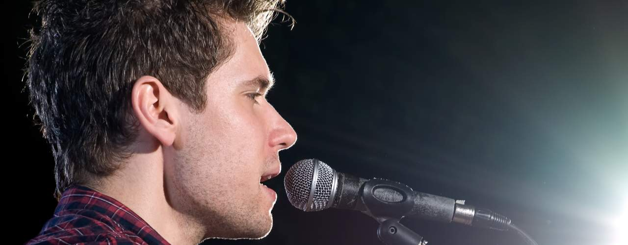 man singing close to microphone up close shot side of head