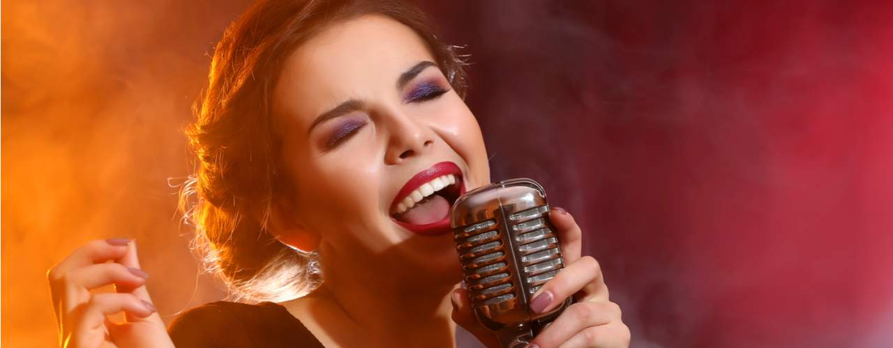 olive skinned woman with lipstick and makeup singing into microphone smoky background orange and red