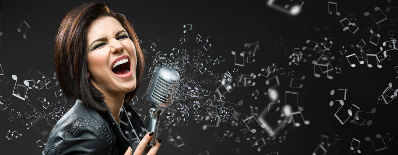 girl in black clothes singing into mic loudly