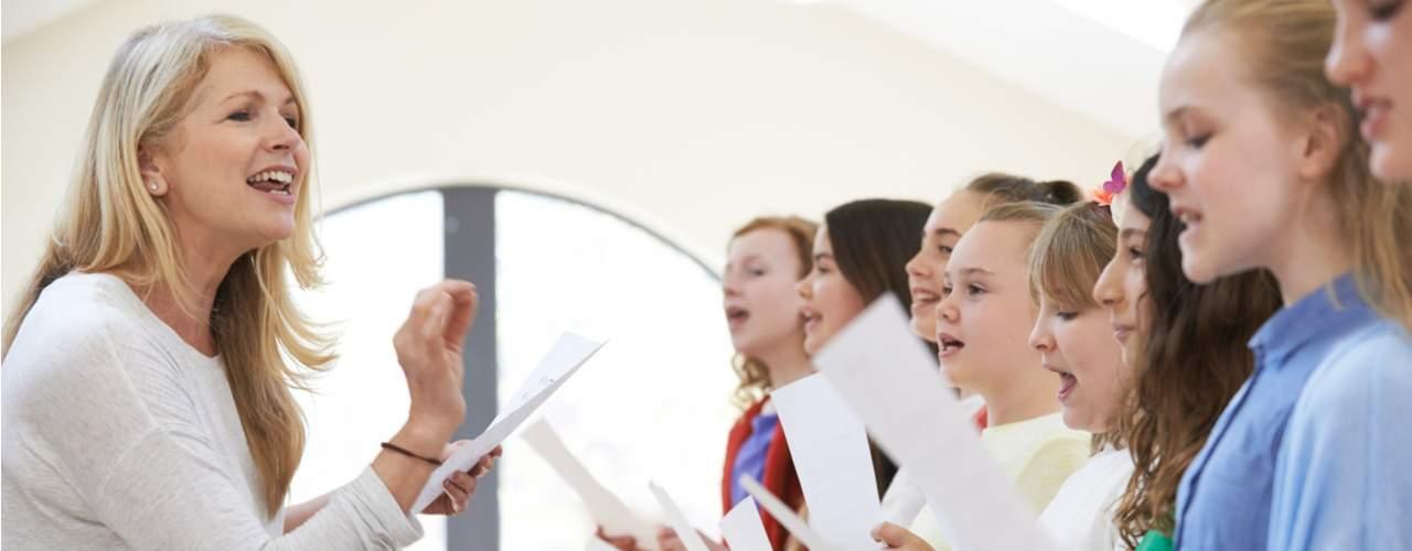 woman singing teacher enunciating to singing students in line