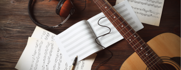a guitar with some guitar music sheets behind it