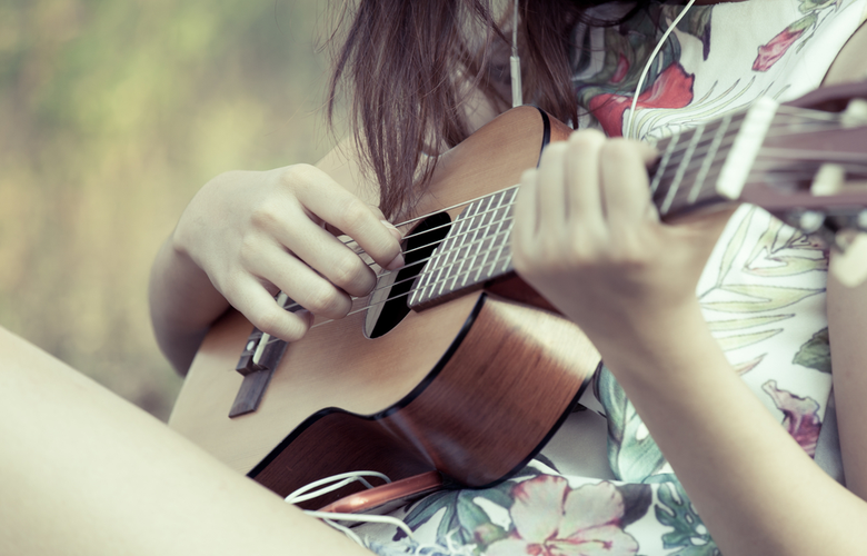 showing what a guitarlele looks like with girl playing it